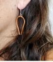 Wearing modern copper horseshoe earrings