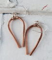 modern copper horseshoe earrings on white distressed trunk