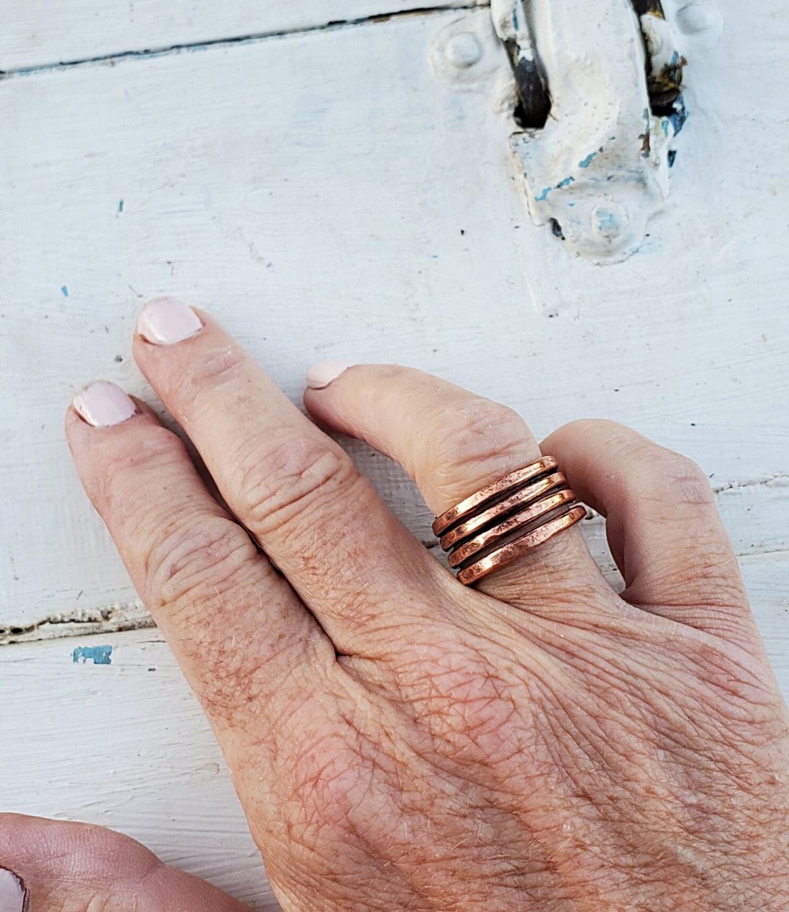 Wearing copper coil ring with white distressed wood background