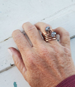 wearing a copper coil ring stacked with blue crystal copper ring with wood background