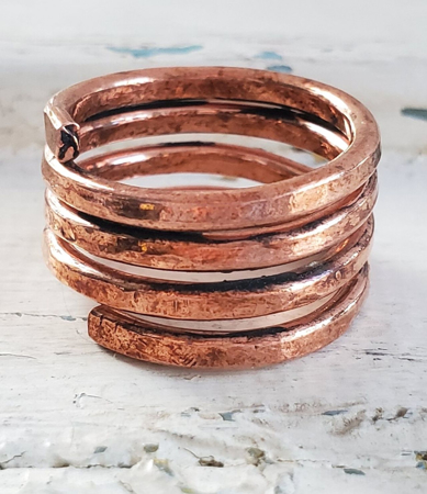hand forged copper coil ring on white distressed wood