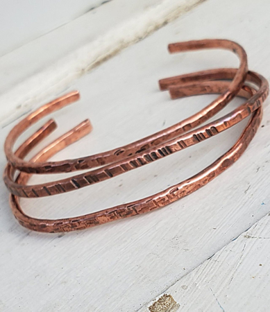 Hand forged copper cuff stack on white distressed wood