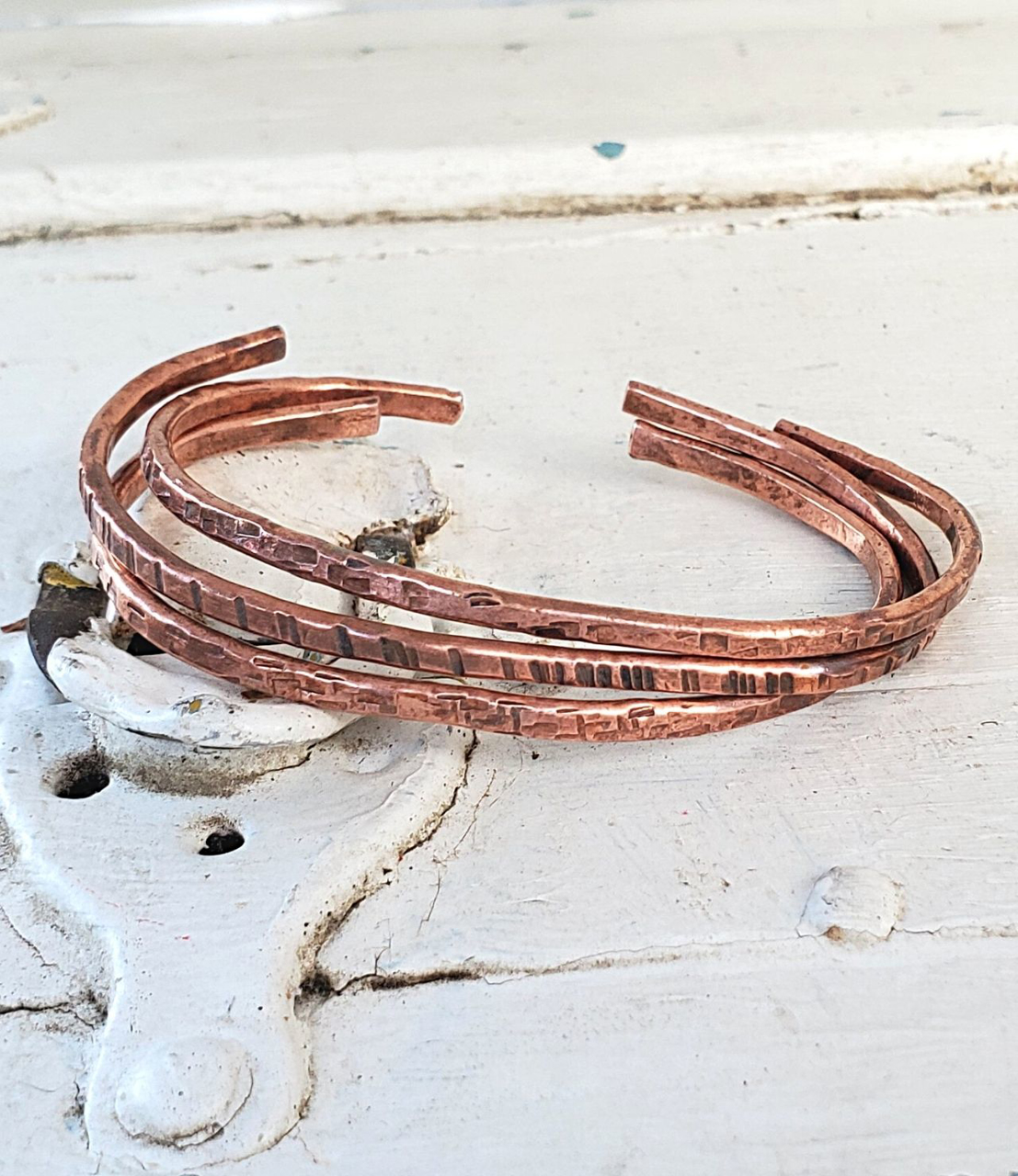casual copper cuff stack on distressed white wood