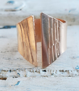 handcrafted bronze crevice ring on white distressed wood