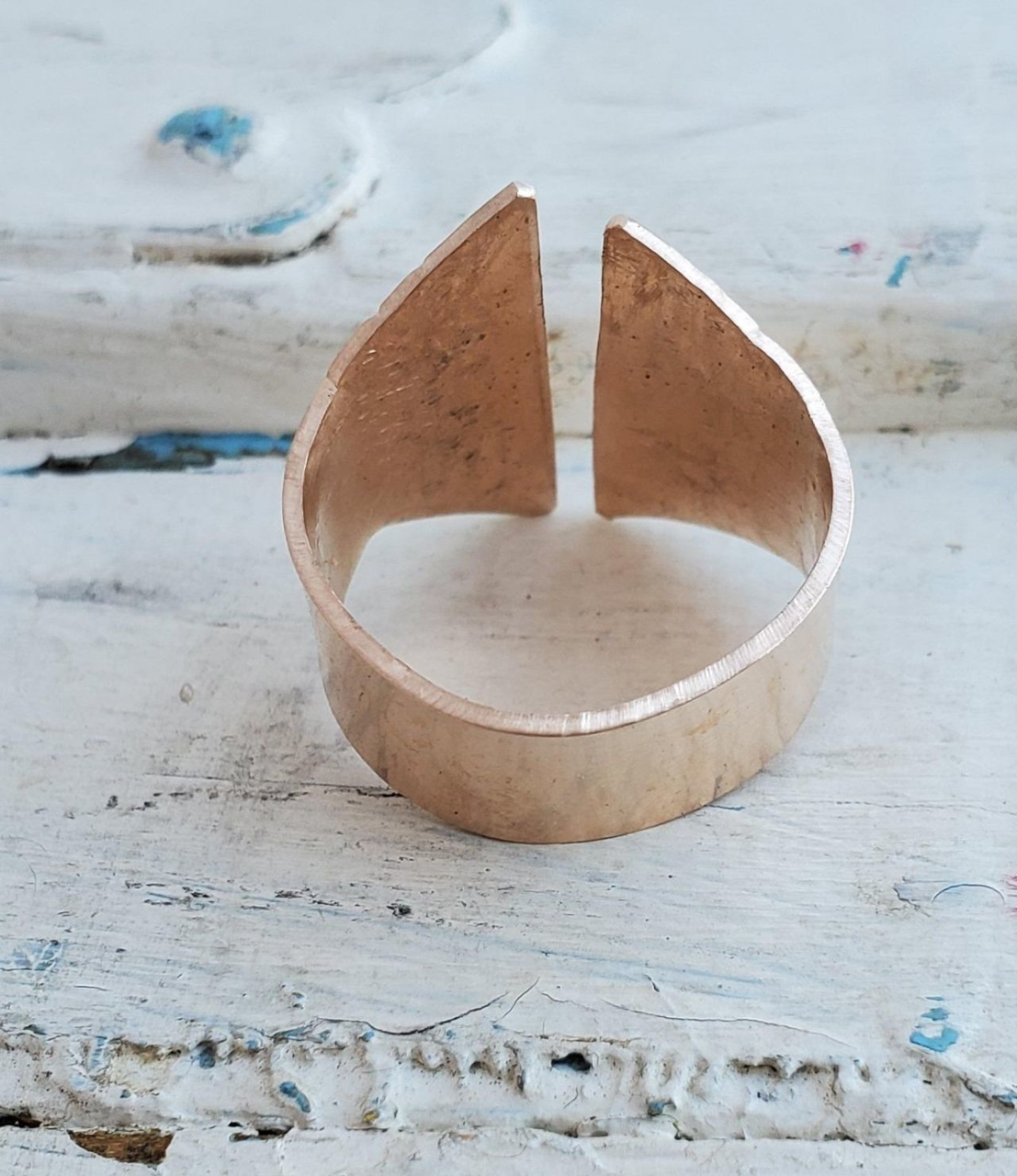 backside of bronze crevice ring on white distressed wood