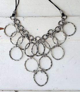 Textured silver circle bib necklace on white trunk