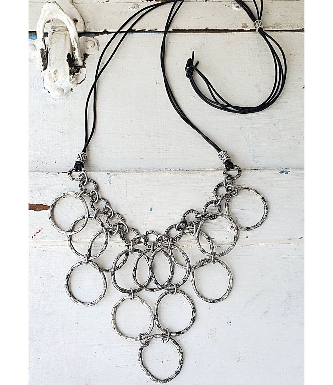 full view silver circle bib necklace on white distressed wood