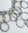 close up silver circle bib necklace on white distressed wood