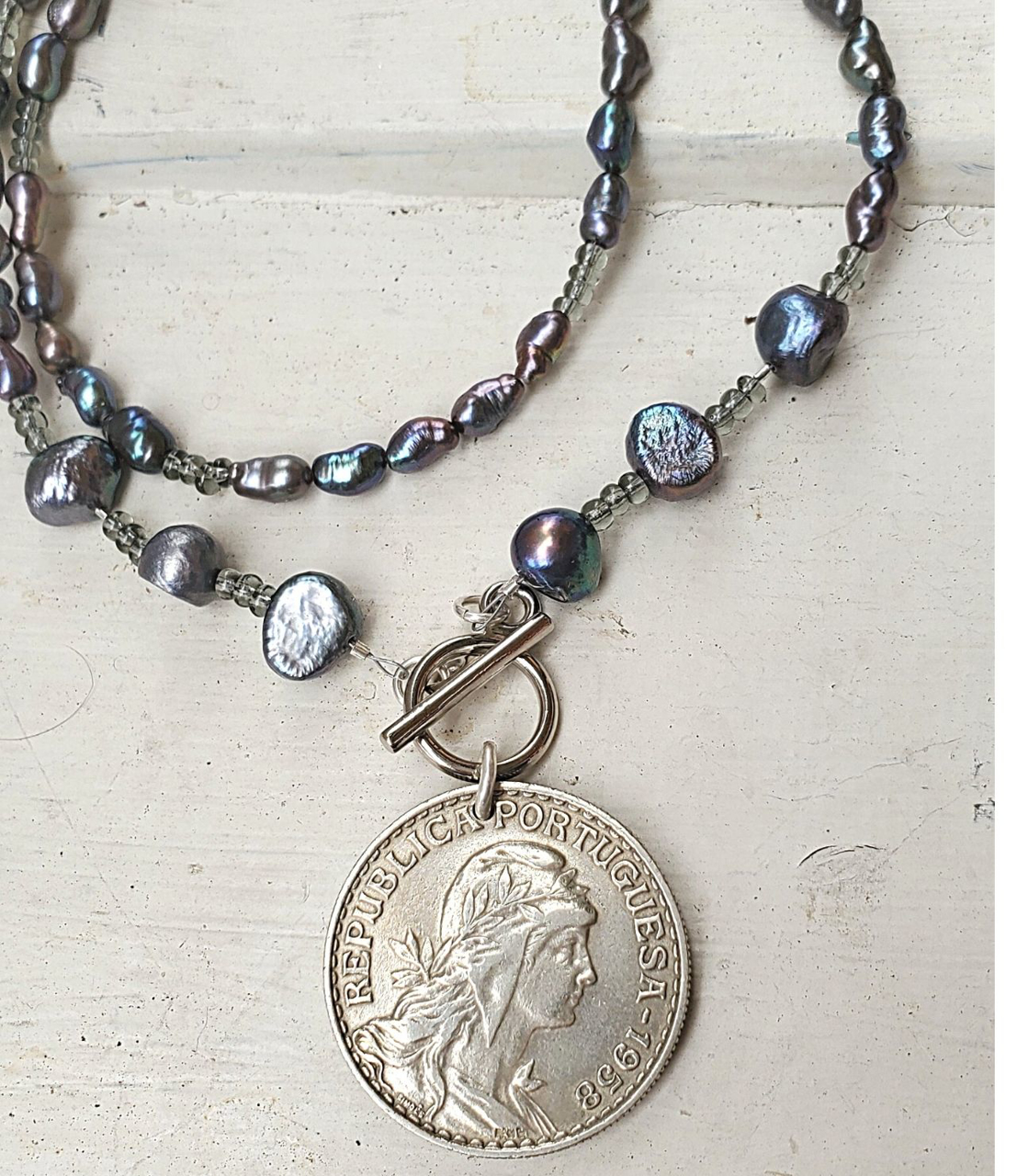 on white wood Portual coin peacock pearl necklace