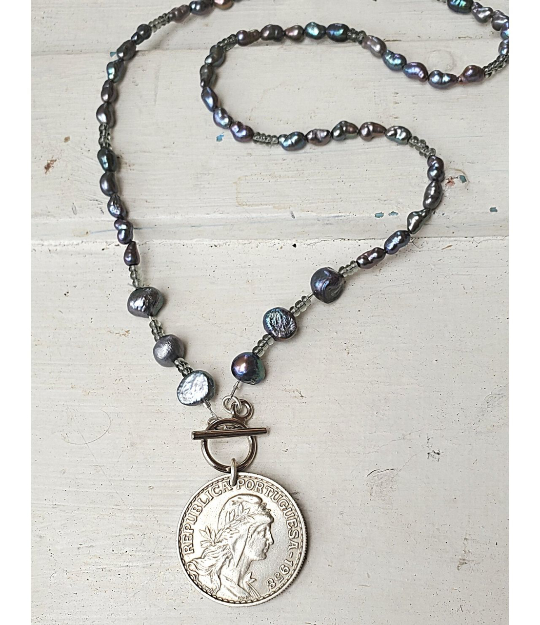 Blue-gray  pearl 1958 Portuguese coin necklace on white distressed wood