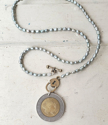Italian coin blue pearl necklace on white wood
