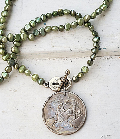 Silver Columbian Coin green pearl necklace on white wood
