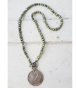 Full view  Silver Columbian Coin green pearl necklace on white wood