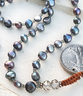 Blue-gray pearl necklace with a silver French coin on white wood
