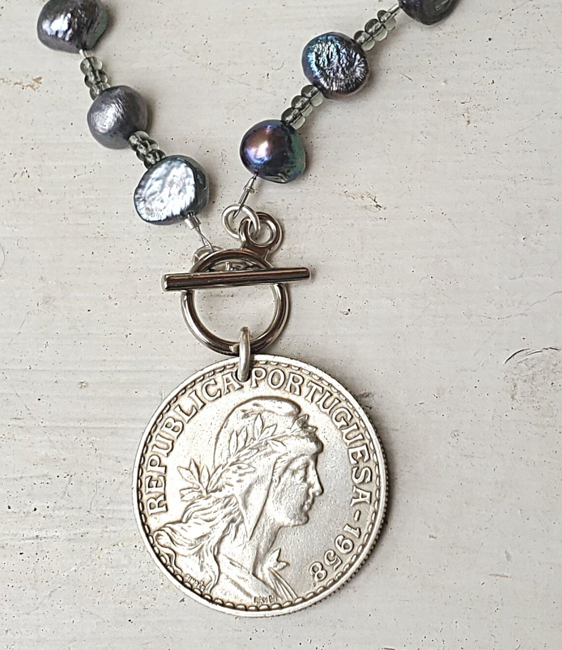up close Blue-gray pearl necklace with a silver French coin on white wood