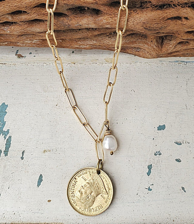 Gold chain coin necklace with white pearl on white wood