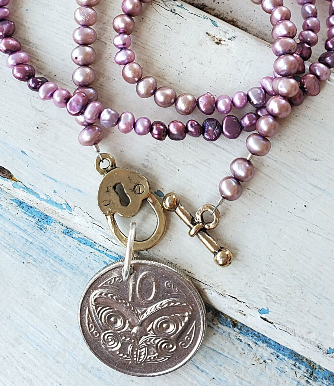 Silver New Zealand purple pearl coin necklace on white distressed wood
