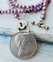 1980 Silver New Zealand purple pearl coin necklace on white distressed wood