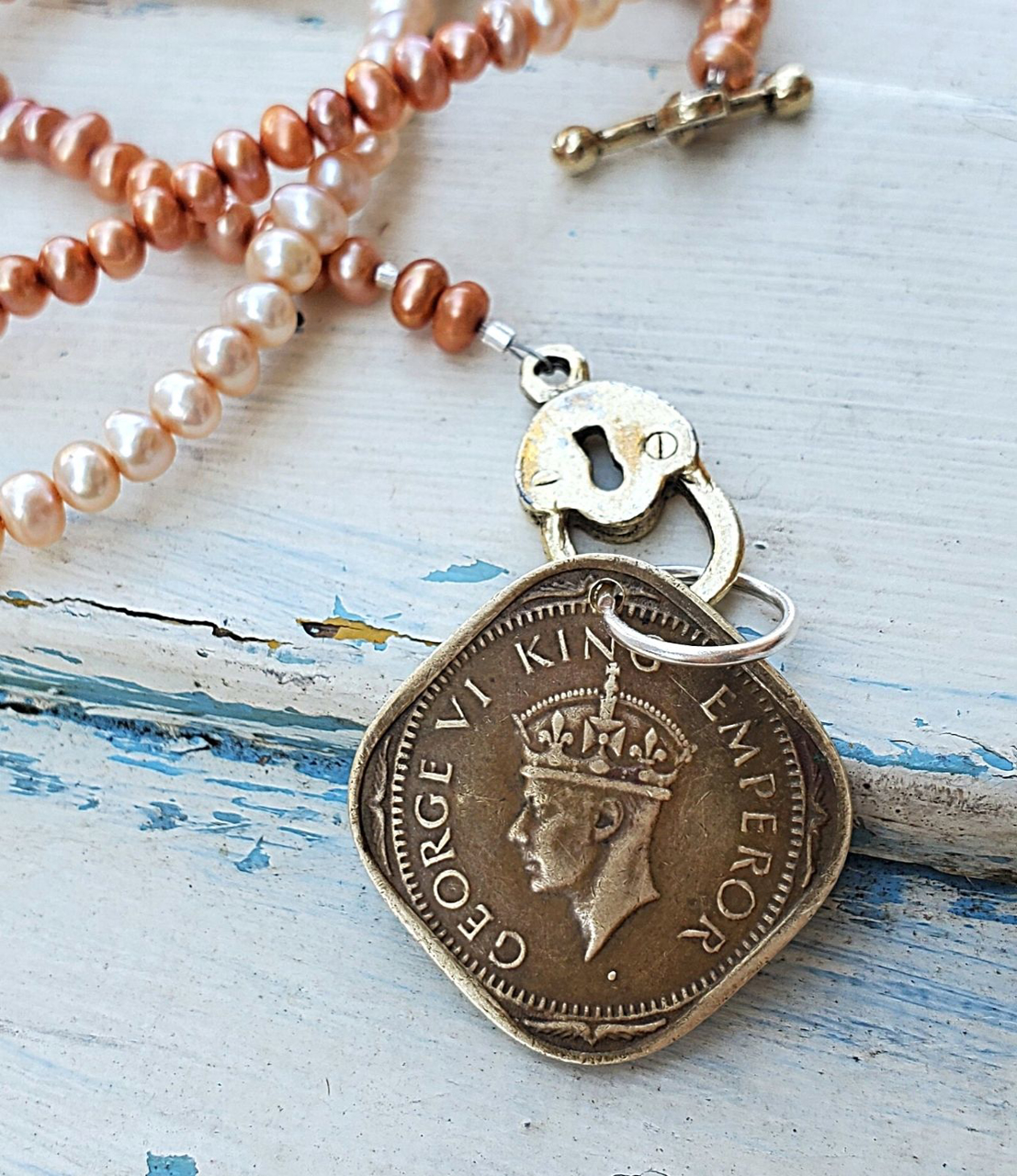 Diamond shaped old India coin pearl necklaceon white wood