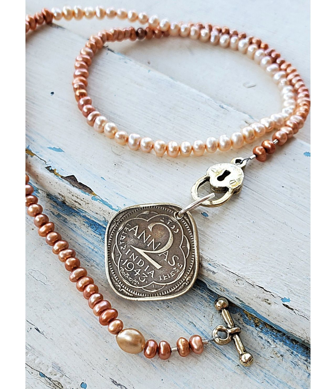 old gold India coin pearl necklace on white distressed wood