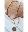 gold India coin pearl necklace full view on white distressed wood