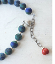 Bright red coral stone on back of blue gemstone necklace