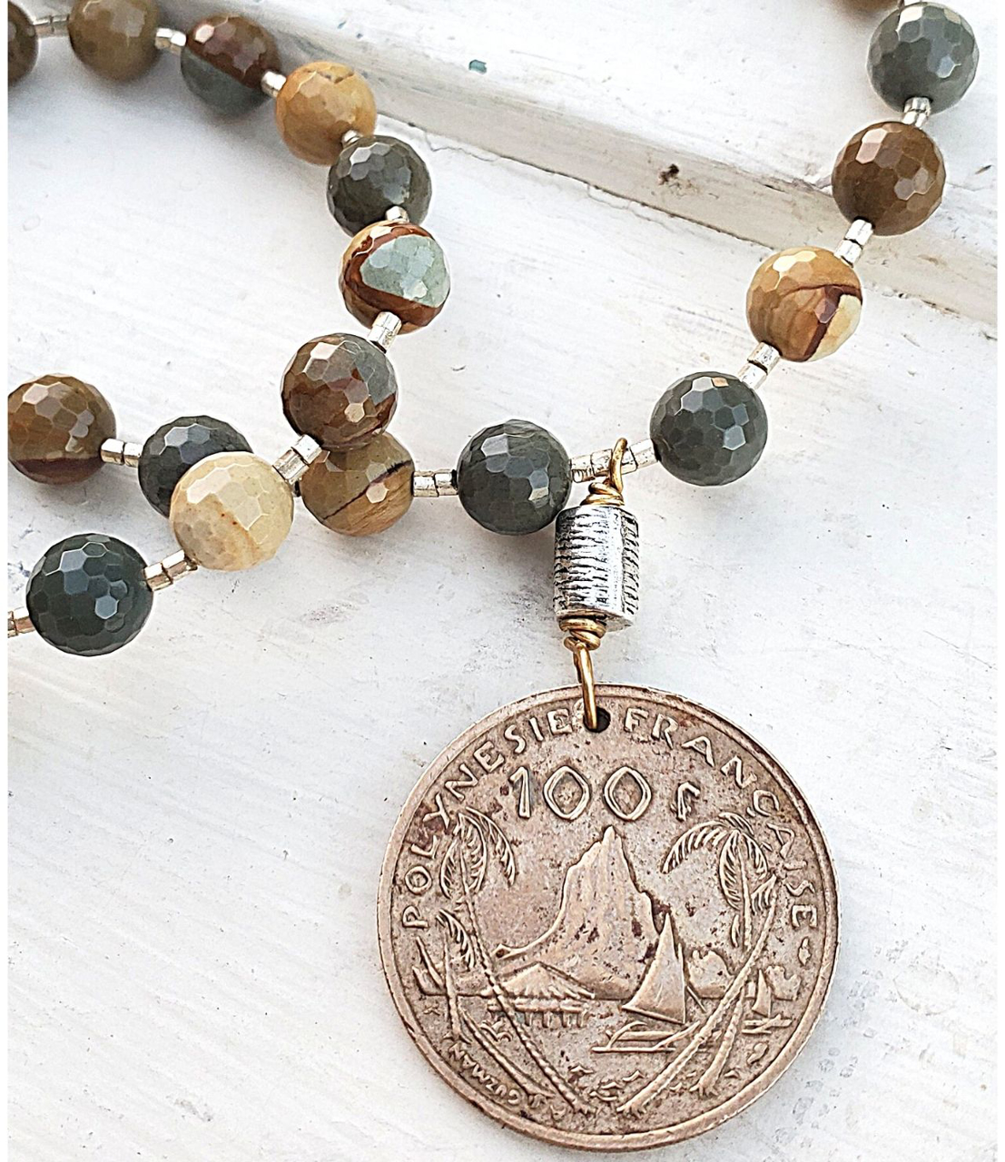 Detailed old coin earthy gemstone necklace on white distressed wood