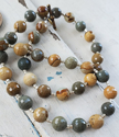 Brown, tan, greenish gray gemstones on white wood
