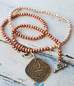 Indian coin pearl necklace on white distressed wood