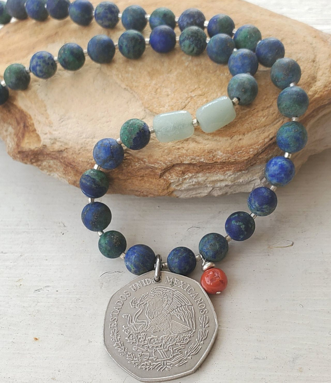 Old silver coin vibrant gemstone necklace on stone