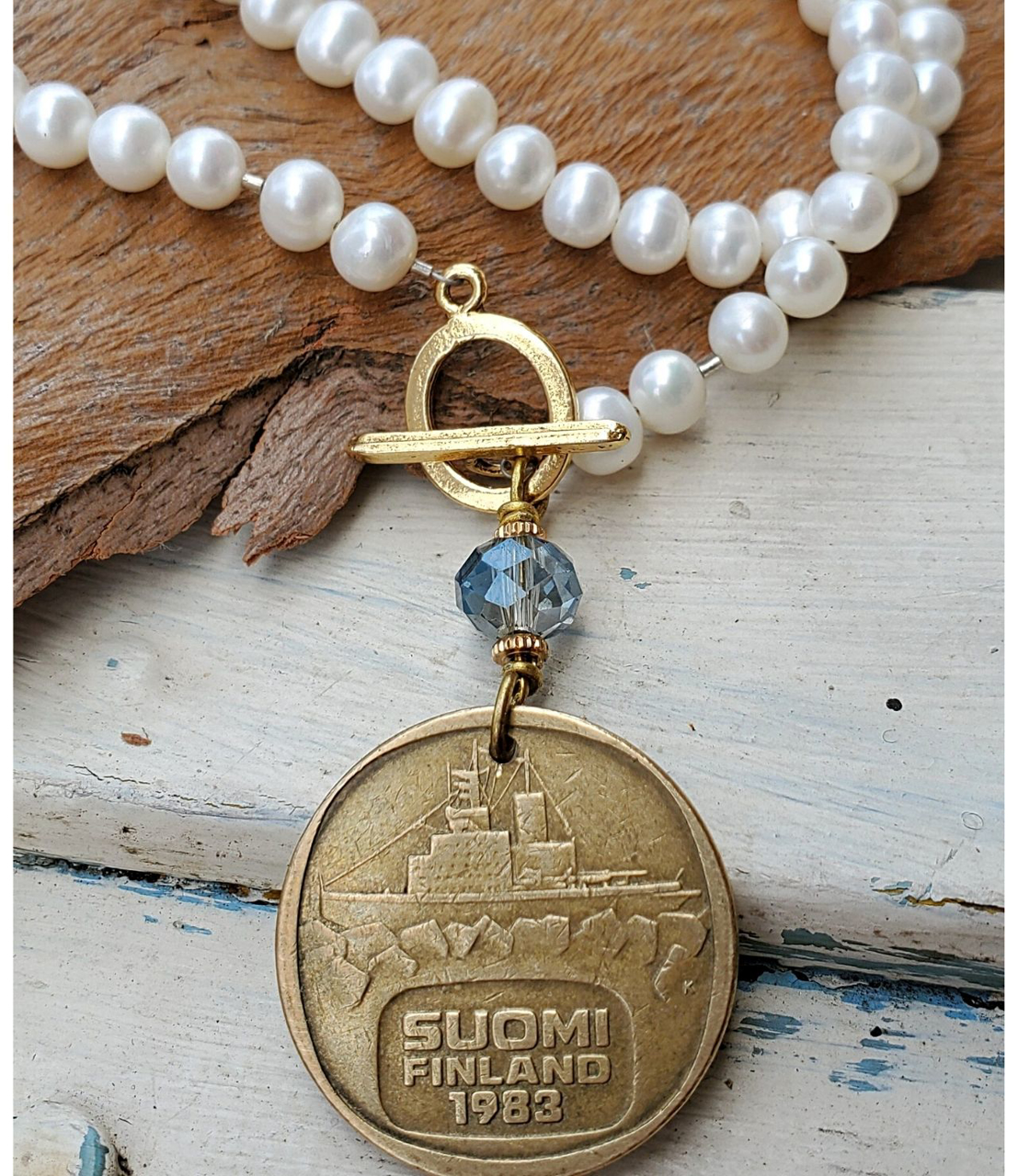 White pearl-gold-Finland coin necklace on wood