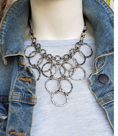 artsy Silver chain bib necklace on mannequin with jean jacket