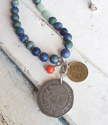 Double coin necklace with blue red gemstones close up