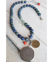 Blue red aqua gemstone coin necklace on white trunk