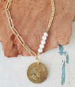 Mixed gold chain pearl coin necklace on white wood