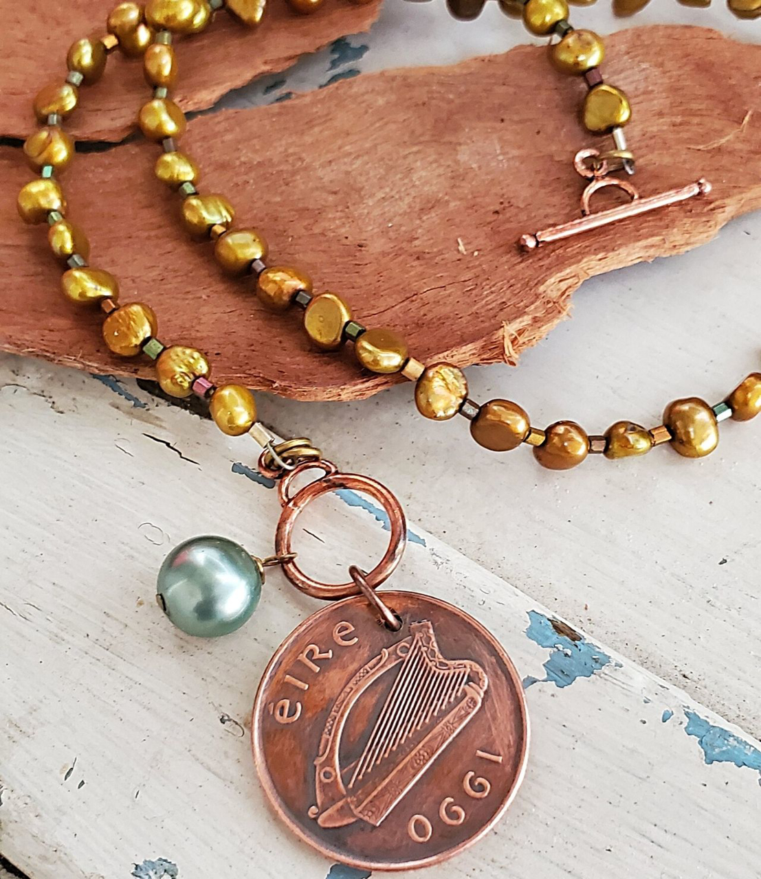 Irish coin pearl necklace on wood
