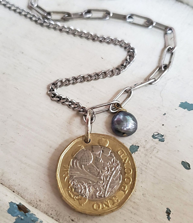 Mixed metal coin and chain necklace on white wood