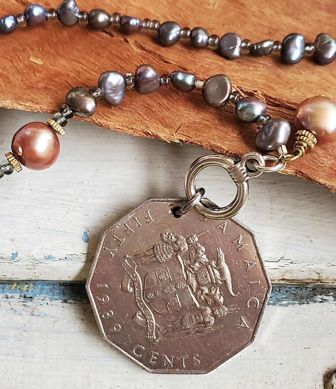 Silver Jamaica coin pearl necklace on wood