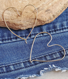 Gold heart hoop earrings on denim with rock