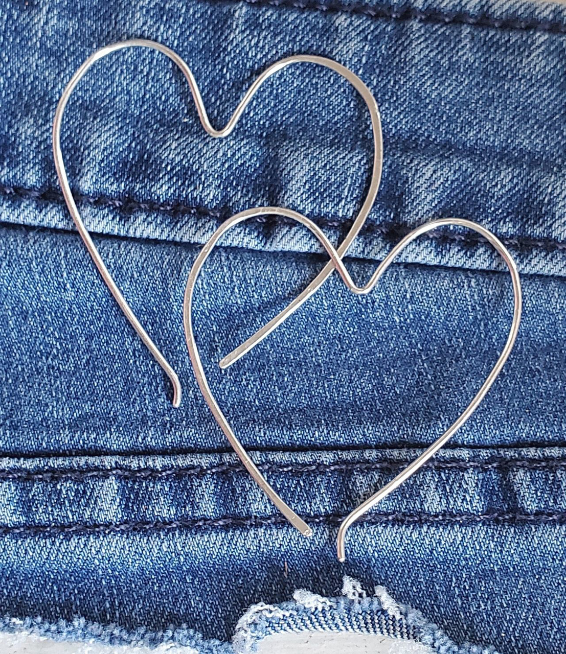 Silver heart hoop earrings on denim