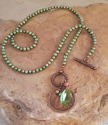 Green pearl, crystal old Irish coin necklace on rock