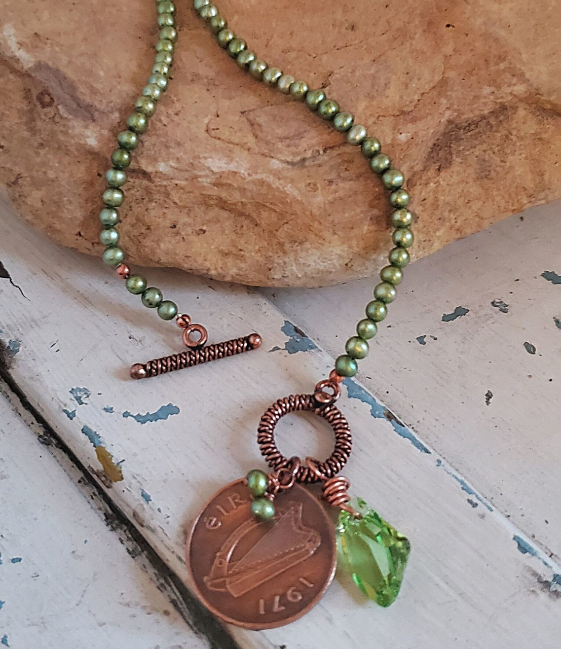 irish coin Green pearl, crystal necklace on rock