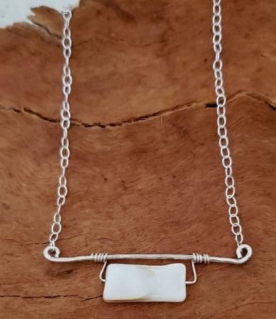 White gemstone siilver bar necklace on wood