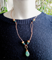 Turquoise black tan gemstone copper loop necklace on black top on mannequin