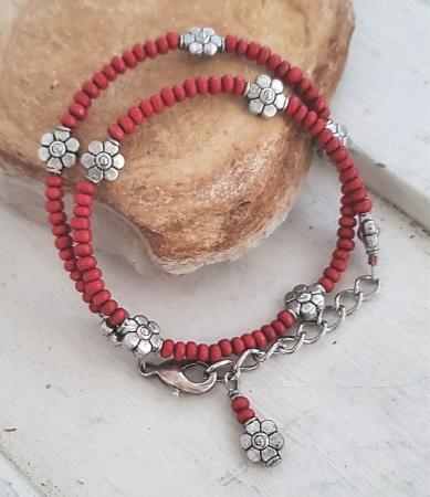 Red bead silver flower bracelet on rock