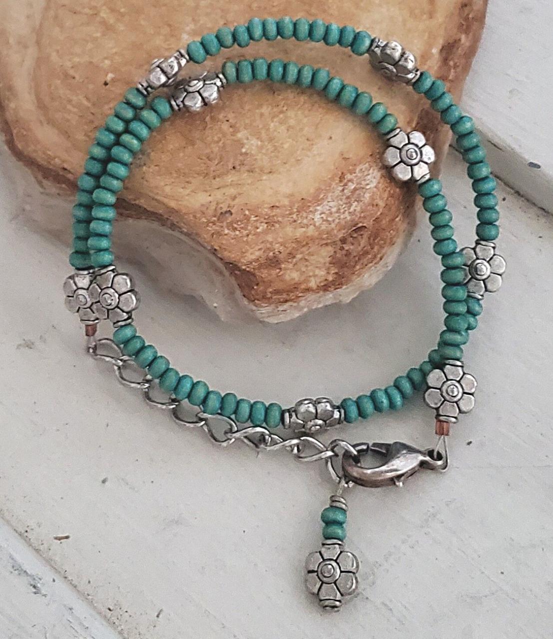 Turquoise wood beads & silver flower bracelet on a rock