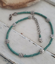 Turquoise wood beads & silver flower choker necklace on white wood