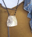 Black chain brass sun necklace on mannequin