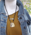 Mannequin with jean jacket wearing layered brass and black artisan necklaces