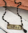 Brass bliss bar necklace with black beaded chain on wood